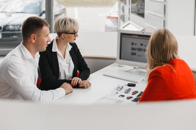 Bovenaanzicht kantoor tijdens een deal tussen dealer en een familie paar dat een auto koopt Premium Foto