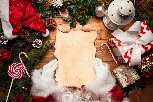 Bovenaanzicht kerstman controleert zijn lijst Gratis Foto
