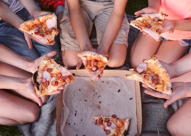 Bovenaanzicht kinderen eten een stuk pizza Gratis Foto