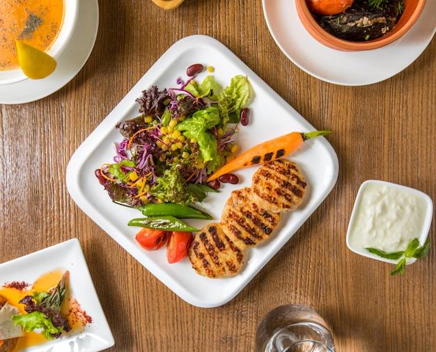 Bovenaanzicht kip filet cotlets en salade met yoghurt. Gratis Foto