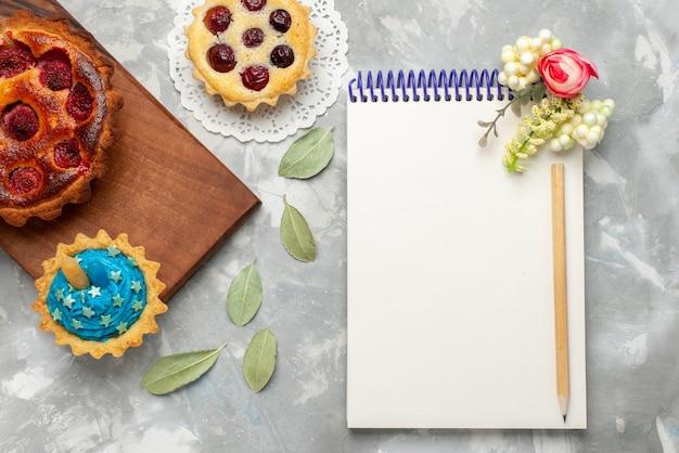 Bovenaanzicht kladblok en taarten op de lichte achtergrond cake taart fruit zoete suiker bakken Gratis Foto