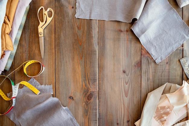 Bovenaanzicht kleermaker werkplek achtergrond met stof Gratis Foto