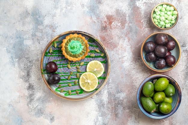 Bovenaanzicht kleine cake met fruit en thee Gratis Foto