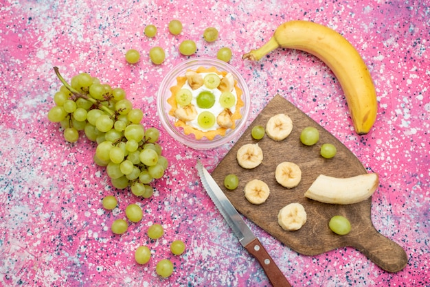 Bovenaanzicht kleine cake met verse druiven en bananen op het heldere oppervlak fruitcake frisse zachte kleur Gratis Foto