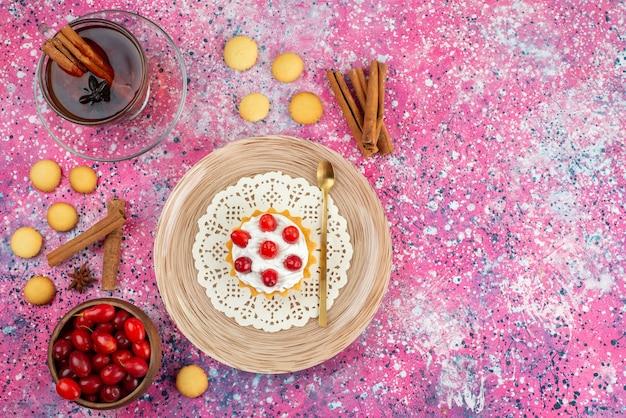 Bovenaanzicht kleine cake met verse room en vers fruit, samen met kaneel en kopje thee op het heldere bureau cake zoet Gratis Foto
