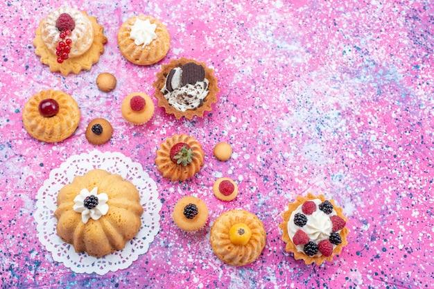 Bovenaanzicht kleine heerlijke taarten met room samen met verschillende bessen op de lichte achtergrond cake koekje bessen zoet bakken Gratis Foto