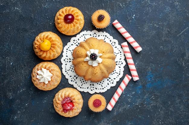 Bovenaanzicht kleine heerlijke taarten samen met roze stok snoepjes op de donkere achtergrond biscuit cake zoete bak Gratis Foto