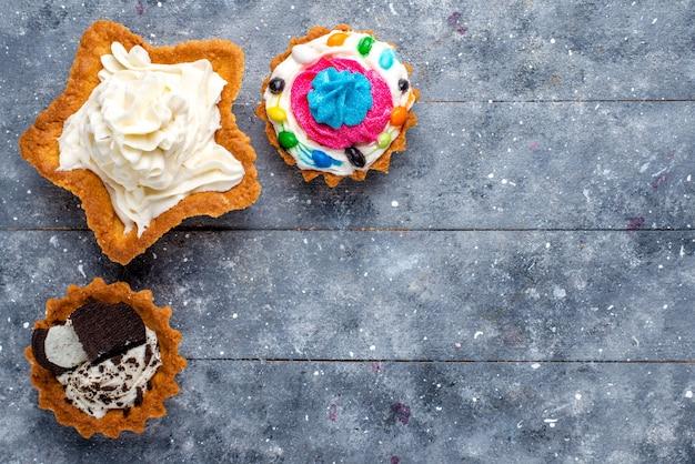 Bovenaanzicht kleine lekkere taarten met room op de foto van de lichttafel snoep zoete kleur cake Gratis Foto