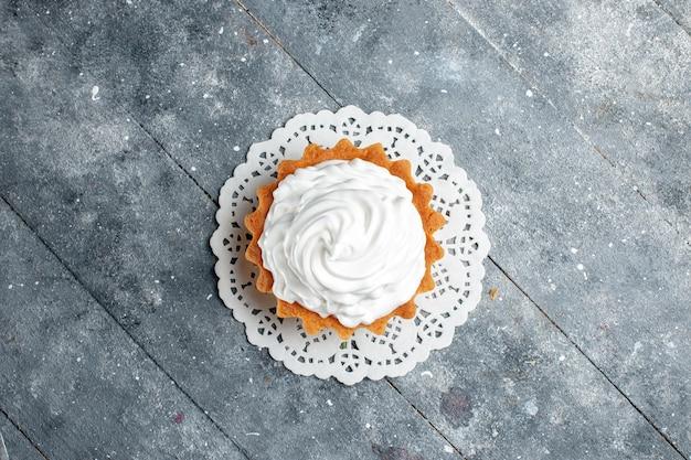 Bovenaanzicht kleine romige cake heerlijk gebakken geïsoleerd op de grijze lichte achtergrond cake biscuit suiker room bakken Gratis Foto