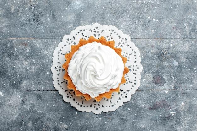 Bovenaanzicht kleine romige cake heerlijk gebakken geïsoleerd op de grijze lichte achtergrond cake koekje zoete suiker room Gratis Foto