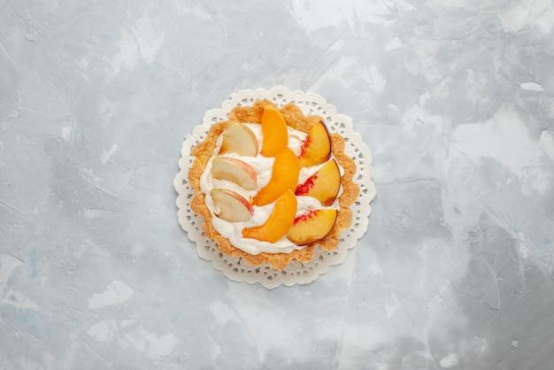 Bovenaanzicht kleine romige cake met gesneden fruit erop op de lichte achtergrond fruitcake zoet koekje Gratis Foto