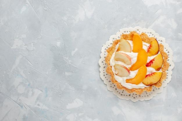 Bovenaanzicht kleine romige cake met gesneden fruit erop op de witte achtergrond fruitcake zoet koekje Gratis Foto