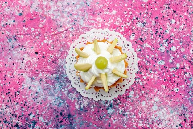 Bovenaanzicht kleine romige cake met gesneden fruit op de gekleurde achtergrond cake zoete suiker bakken kleurenfoto Gratis Foto