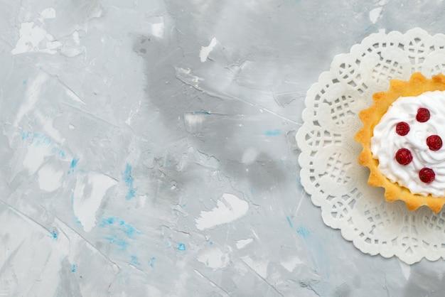Bovenaanzicht kleine romige cake met rood fruit op het grijze oppervlak zoet Gratis Foto