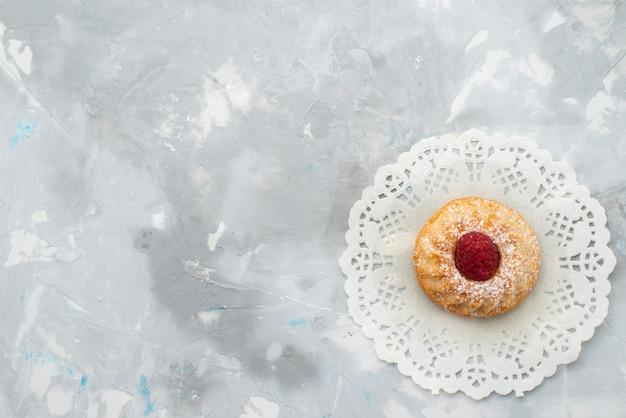Bovenaanzicht kleine slagroomtaart met framboos op het lichte oppervlak fruit zoet Gratis Foto