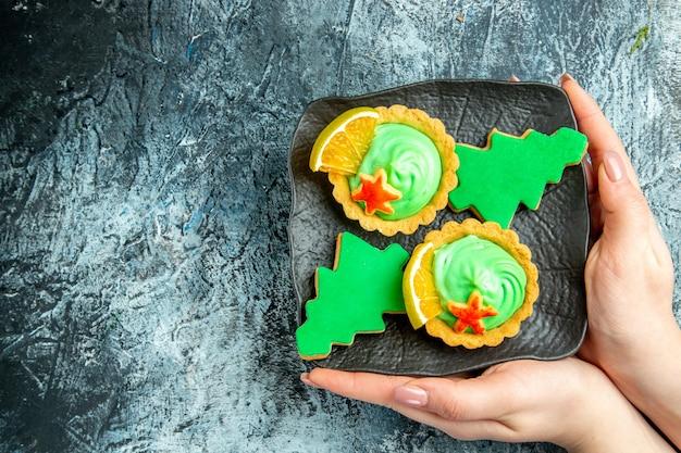 Bovenaanzicht kleine taartjes kerstboom koekjes op zwarte plaat in vrouwelijke hand op grijze tafel vrije ruimte Gratis Foto