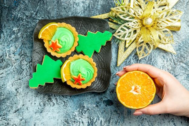 Bovenaanzicht kleine taartjes kerstboom koekjes op zwarte plaat xmas ornament gesneden sinaasappel in vrouw hand op grijze tafel Gratis Foto