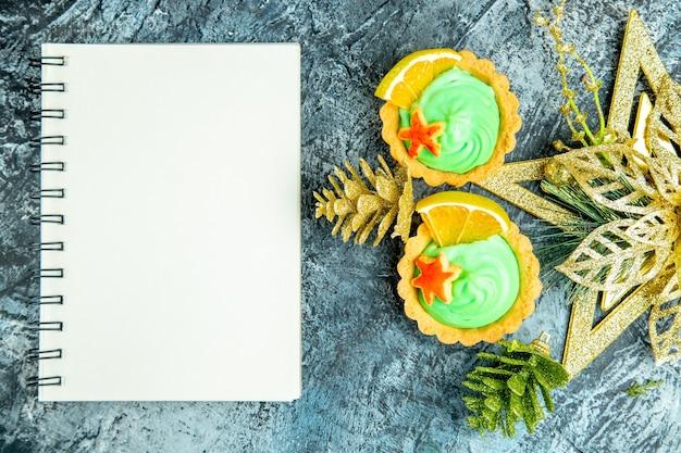 Bovenaanzicht kleine taartjes met groene banketbakkersroom xmas ornamenten notebook op grijze tafel Gratis Foto
