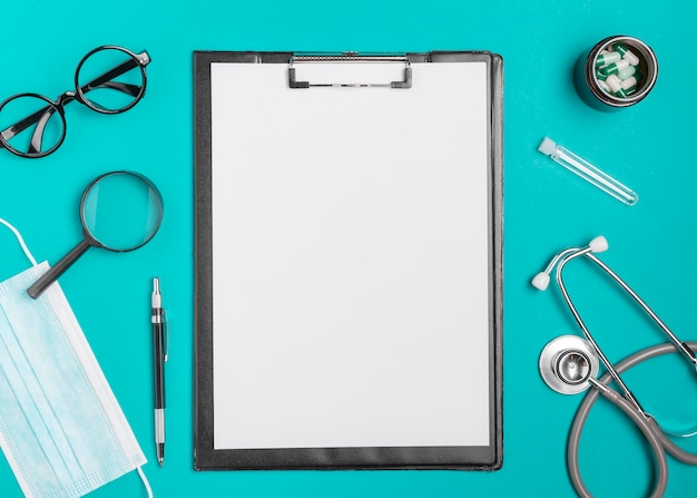 Bovenaanzicht klembord omgeven door een stethoscoop Gratis Foto