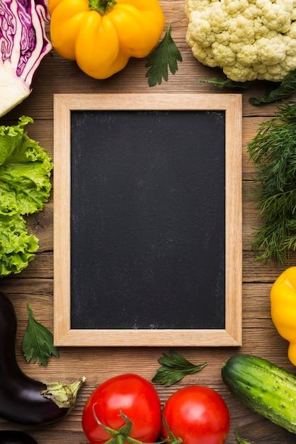 Bovenaanzicht kleurrijke achtergrond met groenten en bord Gratis Foto