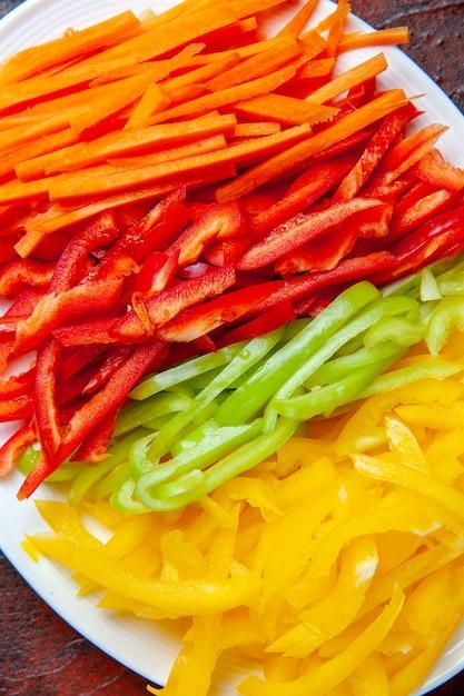 Bovenaanzicht kleurrijke gesneden paprika op witte plaat Gratis Foto