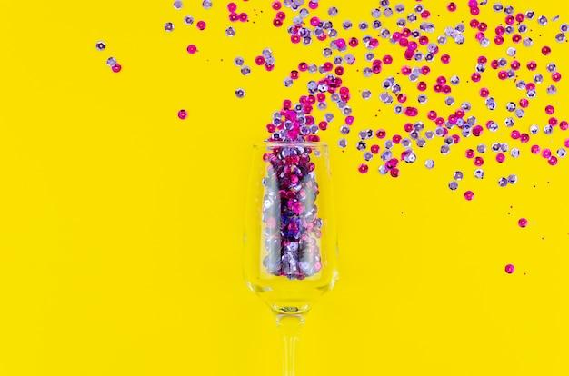 Bovenaanzicht kleurrijke pailletten in een wijnglas Gratis Foto