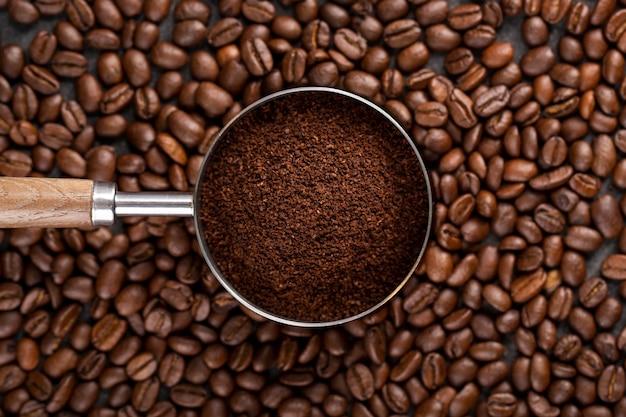 Bovenaanzicht koffie poeder in zeef op koffiebonen Gratis Foto
