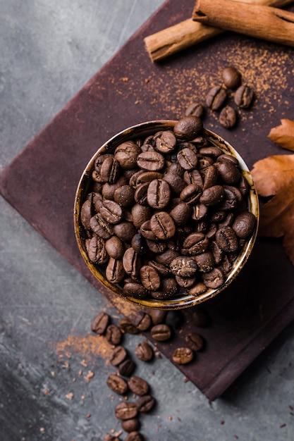 Bovenaanzicht koffiebonen in beker op snijplank met kaneel Gratis Foto