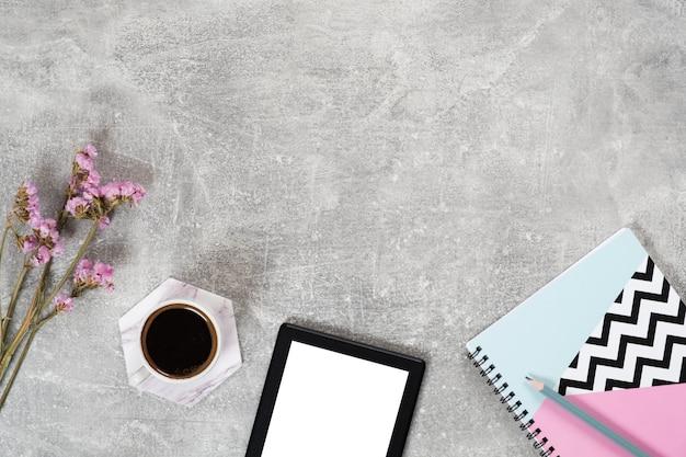 Bovenaanzicht koffiekopje, e-book reader, bloemen, papieren notitieblok op betonnen ondergrond. Premium Foto
