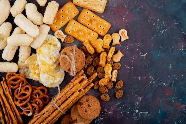 Bovenaanzicht kopie ruimte gezouten koekjes met paneermeel en breadsticks op een roze en blauwe achtergrond Gratis Foto