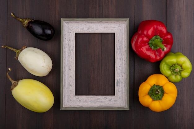 Bovenaanzicht kopie ruimte grijs frame met gekleurde paprika witte en zwarte aubergines op houten achtergrond Gratis Foto