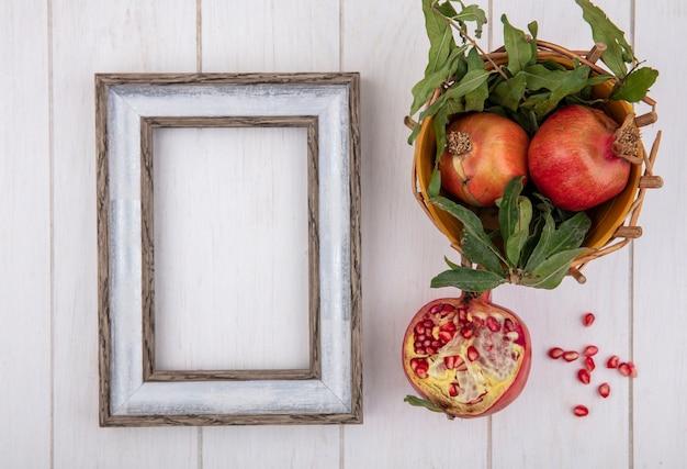 Bovenaanzicht kopie ruimte grijs frame met granaatappels en takken van bladeren in mand op witte achtergrond Gratis Foto