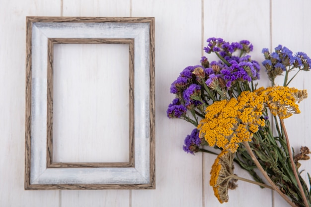 Bovenaanzicht kopie ruimte grijs frame met violet gele wilde bloemen op witte achtergrond Gratis Foto