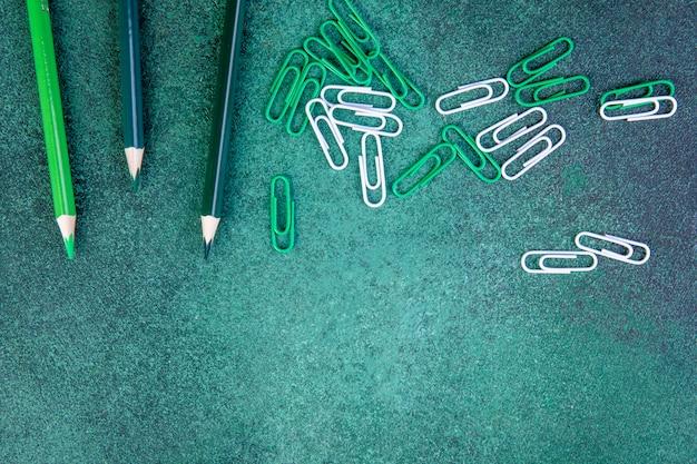 Bovenaanzicht kopie ruimte groene potloden met groene en witte paperclips op een groene achtergrond Gratis Foto