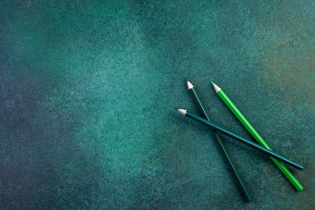 Bovenaanzicht kopie ruimte groene potloden op een groene achtergrond Gratis Foto