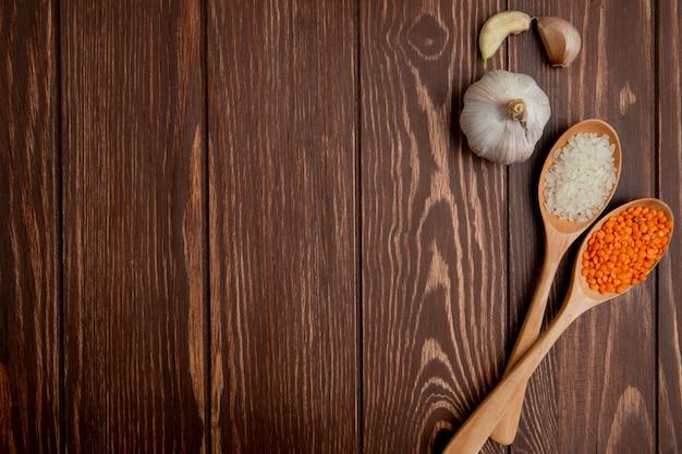 Bovenaanzicht kopie ruimte knoflook met een lepel linzen en rijst op een houten achtergrond Gratis Foto