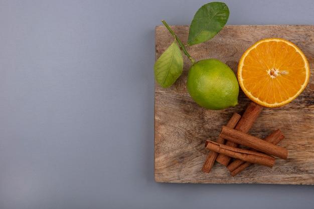 Bovenaanzicht kopie ruimte limoen met schijfje sinaasappel en kaneel op een snijplank op een grijze achtergrond Gratis Foto