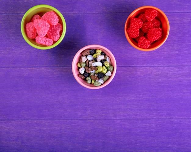Bovenaanzicht kopie ruimte marmelade met chocolade stenen in schoteltjes voor jam op een paarse achtergrond Gratis Foto
