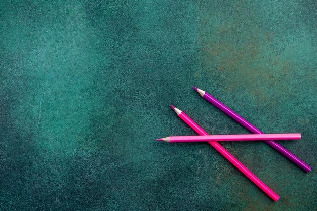 Bovenaanzicht kopie ruimte roze potloden op groene achtergrond Gratis Foto
