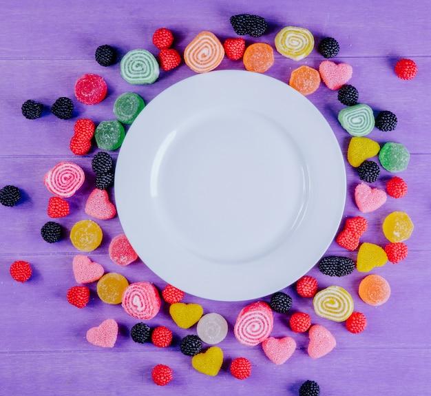 Bovenaanzicht kopie ruimte witte plaat met veelkleurige marmelade rond op een lichtpaarse achtergrond Gratis Foto