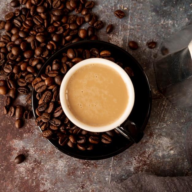 Bovenaanzicht kopje koffie met geroosterde bonen Gratis Foto