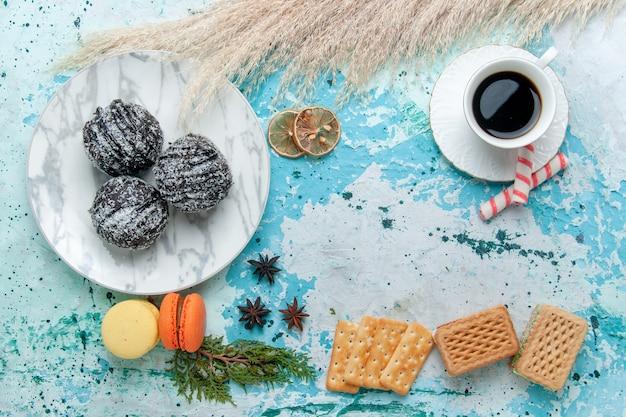 Bovenaanzicht kopje koffie met wafels en chocoladetaart op de blauwe achtergrond cake bakken koekje zoete chocolade suiker kleur Gratis Foto
