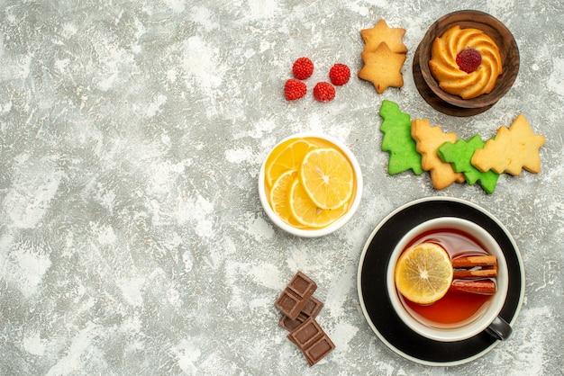 Bovenaanzicht kopje thee koekje en plakjes citroen in kommen kerstboom cookies op grijze oppervlakte vrije ruimte Gratis Foto