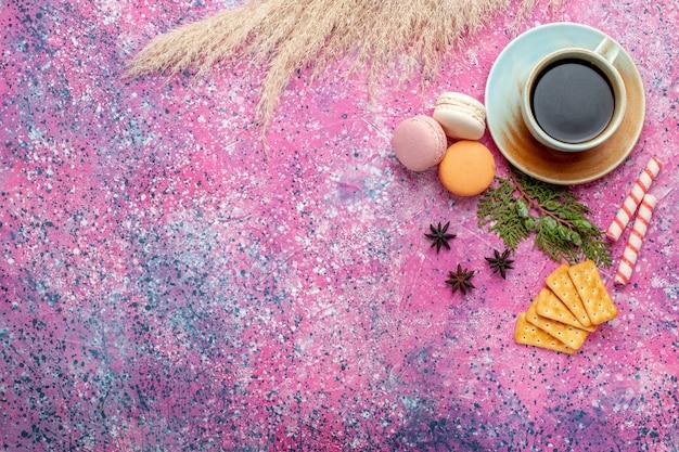 Bovenaanzicht kopje thee met crackers en macarons op lichtroze ondergrond Gratis Foto
