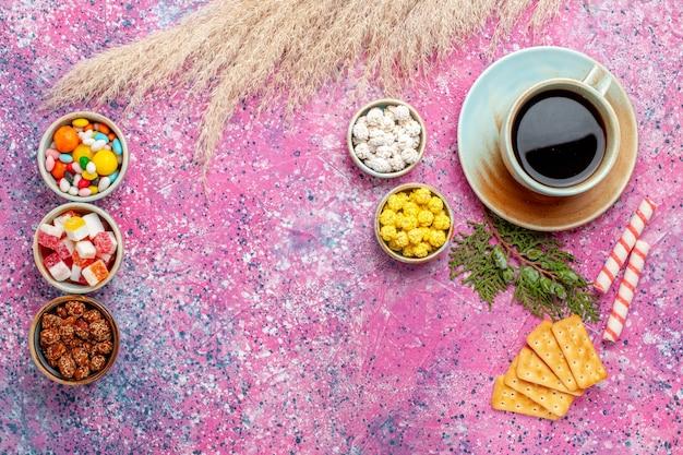 Bovenaanzicht kopje thee met crackers en snoepjes op het roze bureau Gratis Foto