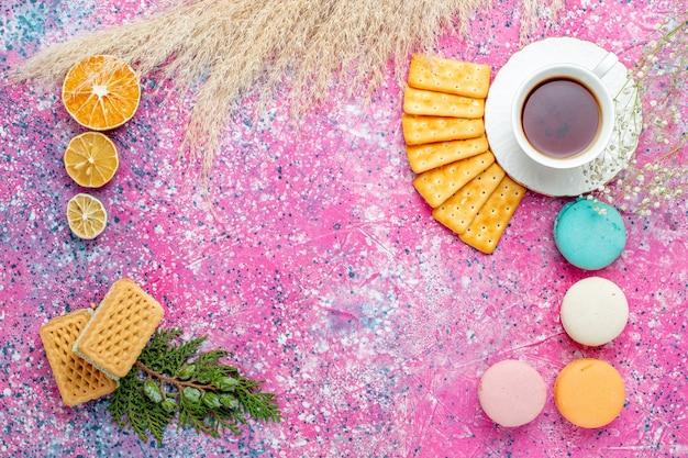 Bovenaanzicht kopje thee met crackers franse macarons en wafels op roze bureau Gratis Foto