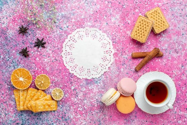 Bovenaanzicht kopje thee met franse macarons en crackers op het lichtroze bureau Gratis Foto
