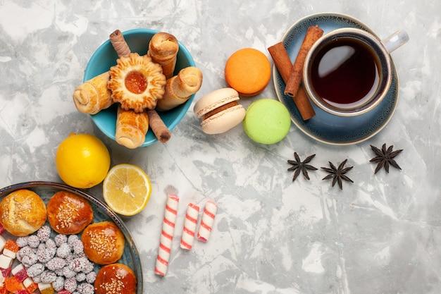Bovenaanzicht kopje thee met gebak en macarons op witte ondergrond Gratis Foto