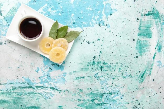 Bovenaanzicht kopje thee met gedroogde ananasringen op lichtblauw oppervlak Gratis Foto