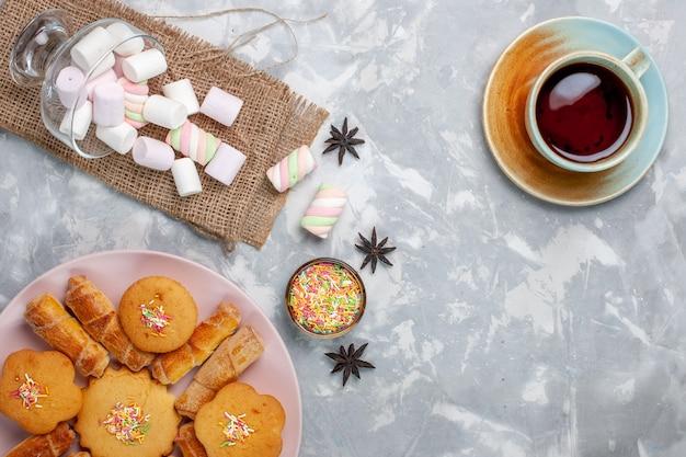 Bovenaanzicht kopje thee met heerlijke kleine marshmallows en gebak op wit bureau Gratis Foto